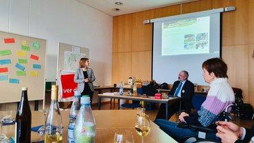 Vortragende Katrin Eder, im Hintergrund Fragentafel, Mobilitätskarte und Vortrag Urbanre Mobilität für Mainz